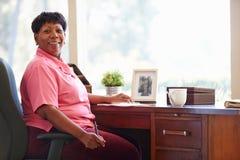 Scrittura matura della donna in taccuino che si siede allo scrittorio Fotografie Stock Libere da Diritti