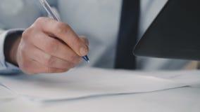 Scrittura premurosa stanca dell'uomo sulla carta e sulla compressa usando in ufficio 4K video d archivio