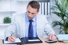 Scrittura professionale dell'uomo d'affari sul suo taccuino Immagine Stock