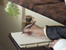 Scrittura saudita della mano dell'uomo su un taccuino fotografia stock
