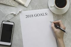 Scrittura 2018 scopi, un telefono cellulare con le cuffie e una tazza del cofee Fotografia Stock