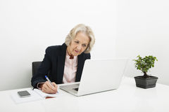 Scrittura senior della donna di affari in libro mentre utilizzando computer portatile allo scrittorio nell'ufficio Fotografie Stock
