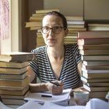 Scrittura seria della donna in un taccuino in una stanza con i lotti dei libri Fotografia Stock Libera da Diritti