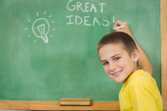 Scrittura sorridente dell'allievo sulla lavagna in un'aula Immagini Stock Libere da Diritti