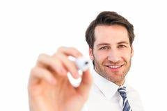Scrittura sorridente dell'uomo d'affari con l'indicatore nero Fotografia Stock
