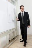 Scrittura sorridente dell'uomo d'affari su un bordo bianco Fotografia Stock Libera da Diritti