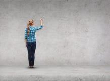 Scrittura sorridente della giovane donna sullo schermo virtuale Fotografia Stock