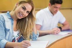 Scrittura sorridente della studentessa durante la classe Fotografie Stock