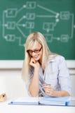 Scrittura sorridente della studentessa sul suo libro Immagine Stock