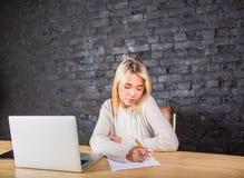 Scrittura su un riassunto, seduta del candidato di giovane donna alla tavola con il computer portatile Fotografia Stock