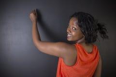 Scrittura sudafricana o afroamericana dell'insegnante della donna sul fondo del bordo del nero del gesso Fotografia Stock Libera da Diritti