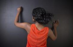 Scrittura sudafricana o afroamericana dell'insegnante della donna sul fondo del bordo del nero del gesso Fotografie Stock Libere da Diritti