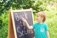 Scrittura sveglia del ragazzino sulla lavagna all'aperto Di nuovo al concetto del banco Immagini Stock