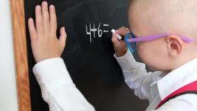Scrittura sveglia del ragazzino sulla lavagna Bambino da scuola elementare con la borsa Concetto di formazione Di nuovo al banco archivi video
