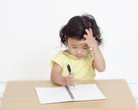 Scrittura sveglia della bambina qualcosa Fotografie Stock