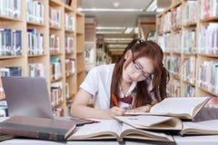 Scrittura sveglia dello studente sul libro in biblioteca Immagine Stock