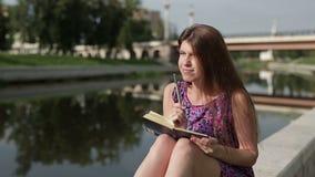 Scrittura sveglia sorridente della giovane donna in taccuino che si siede sul prato inglese archivi video