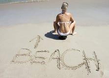 Scrittura tropicale di seduta della sabbia della spiaggia della noce di cocco della donna Immagine Stock