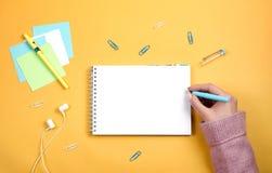 Scriva i pensieri e le idee in un taccuino bianco pulito su un fondo arancio immagini stock libere da diritti
