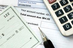 Scriva un assegno per pagare le fatture Fotografia Stock