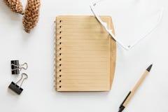 Scrivania bianca con i vetri, la penna, il taccuino ed il cono sopra Fotografia Stock