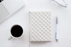 Scrivania bianca con una parte del computer portatile, vetri, caffè Fotografia Stock