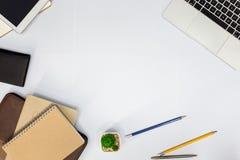 Scrivania bianca tavola con il taccuino in bianco fotografia stock libera da diritti