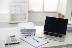 Scrivania che una pila di rapporti della carta per computer funziona Immagini Stock