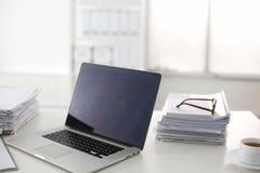Scrivania che una pila di rapporti della carta per computer funziona Fotografie Stock Libere da Diritti