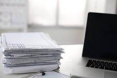 Scrivania che una pila di rapporti della carta per computer funziona Immagini Stock Libere da Diritti