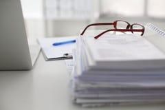 Scrivania che una pila di rapporti della carta per computer funziona Fotografia Stock