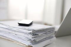 Scrivania che una pila di rapporti della carta per computer funziona Fotografie Stock