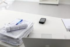 Scrivania che una pila di rapporti della carta per computer funziona Immagine Stock