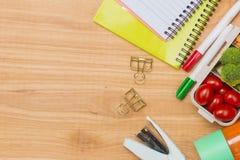 Scrivania con i rifornimenti e scatola di pranzo con le verdure e il almo Immagine Stock Libera da Diritti