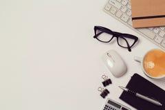 Scrivania con il computer, i taccuini e la tazza di caffè sopra fondo bianco Fotografia Stock Libera da Diritti