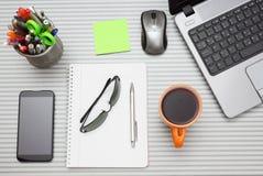 Scrivania con il computer portatile con gli accessori di affari e la tazza di tè Fotografia Stock