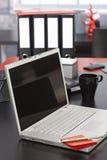 Scrivania con il computer portatile e le cartelle Fotografia Stock
