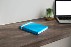 Scrivania con il libro blu della copertura, schermo in bianco sul computer portatile, garde Immagini Stock Libere da Diritti