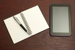 Scrivania con una compressa, il taccuino e una penna Immagine Stock