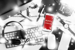 Scrivania dell'area di lavoro con gli elementi essenziali che lavorano roba con il messaggio `` Buon Natale `` Fotografia Stock Libera da Diritti
