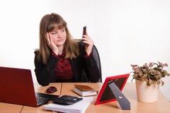 Scrivania di seduta della donna stanca, esaminante telefono immagini stock