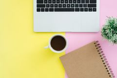 Scrivania di vista superiore con il computer portatile, i taccuini e la tazza di caffè sul fondo di colore pastello Fotografia Stock Libera da Diritti