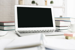 Scrivania sudicia con il computer portatile Fotografie Stock