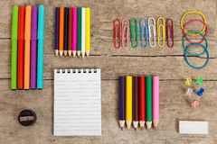 Scrivania variopinta con un blocco note, i pencins ed altre attrezzature Fotografia Stock