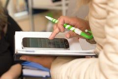 Scrive in un taccuino con un calcolatore Fotografie Stock Libere da Diritti
