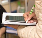 Scrive in un taccuino con un calcolatore Immagine Stock Libera da Diritti
