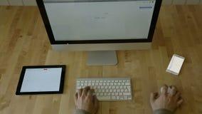 Scrivendo allo scrittorio di legno con la compressa ed il computer portatile archivi video