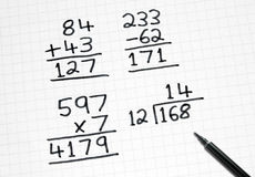Scrivendo le somme semplici di per la matematica sul documento quadrato. Fotografie Stock