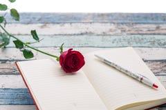 Scrivendo per l'amore: rosa rossa, giornale e penna Fotografie Stock Libere da Diritti