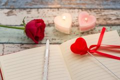 Scrivendo per l'amore: rosa rossa, giornale e penna con le candele Fotografia Stock Libera da Diritti